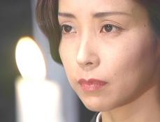 亡き父親の祭壇を見つめる凜子