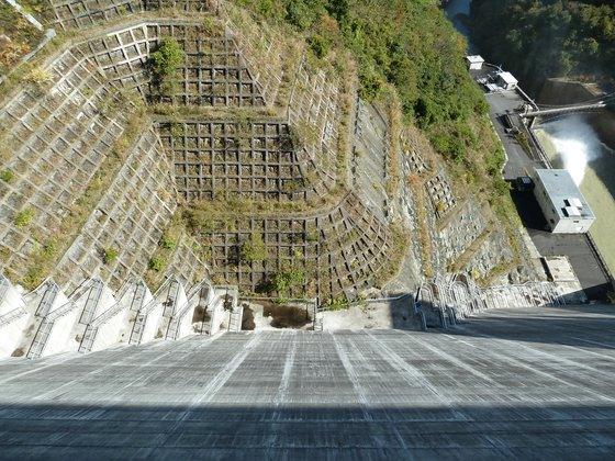 ダムの堰の上から真下を眺める
