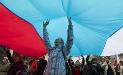 巨大なロシアの国旗を掲げて大声でスローガンを叫ぶ住民ら=クリミア自治共和国の首都シンフェロポリで2014年3月1日、AP