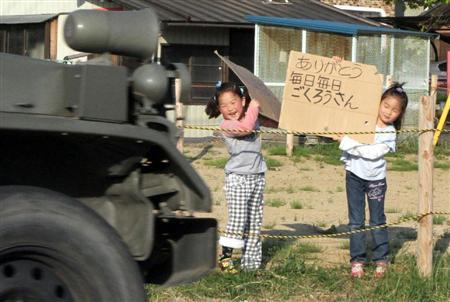 自衛隊の車両が通る度、段ボール紙に書いた感謝のメッセージを掲げる少女たち =平成23年5月24日、福島県川俣町