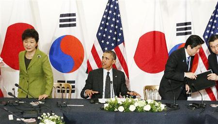 報道陣の撮影が終わり、日米韓3カ国首脳会談に向けて席を立つ(左から)韓国の朴槿恵大統領、オバマ米大統領、安倍首相=25日、オランダ・ハーグ(共同)