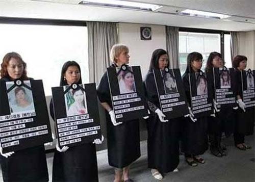 韓国人の夫に殺害された外国人妻の遺影を掲げる女性たち