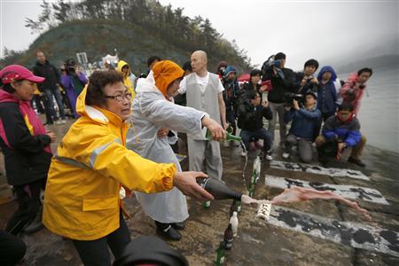 18日、船に閉じ込められた不明者の家族らが転覆現場近くの港で、仏教に基づく儀式を執り行った=韓国南西部・珍島(ロイター)