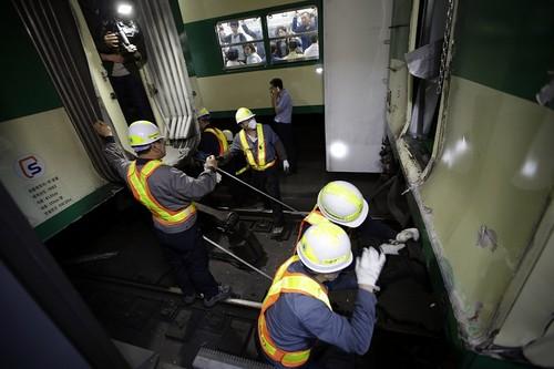 事故車両を切り離す作業員=ソウルで2014年5月2日、AP