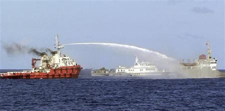 7日、南シナ海でベトナム船(右)に向けて放水する中国船(左)。中央は中国海警局の船=ベトナム沿岸警備隊提供(AP)