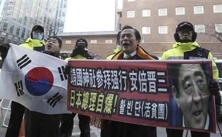 安倍晋三首相の靖国神社参拝を受けて抗議活動する韓国の男性ら。冷え込んだ日韓関係改善の糸口はいまだ見えない=2013年12月27日(AP)