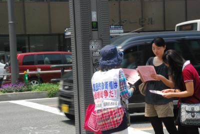 7月1日博多駅前街宣チラシ見ながら熱心に話を聞く若い女性