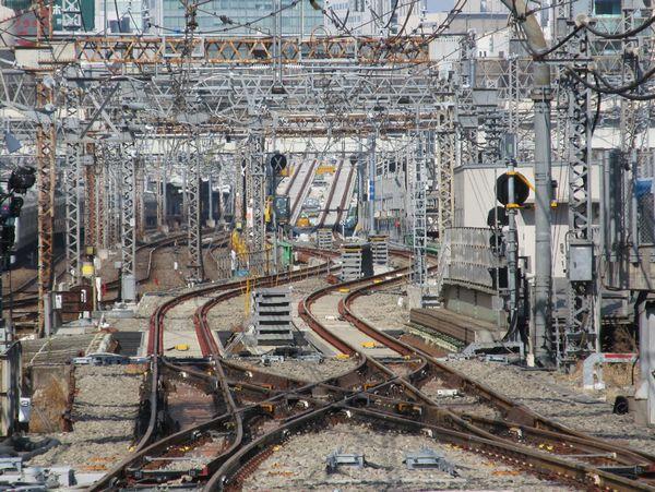 さらに奥をズーム。首都高高架橋の奥に重層高架に向けて急上昇する2本の真新しい線路が見える。