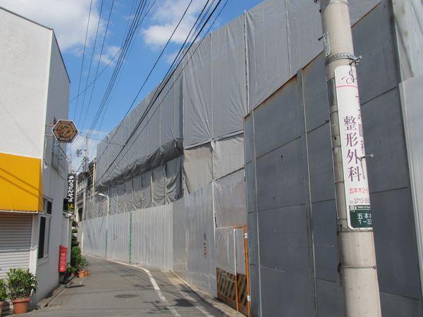 上り線ホームを駅の外から見たところ。壁を撤去するためネットで覆われている。