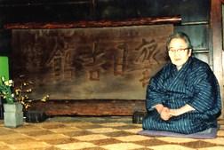 部屋に下された名物看板の横に座る田村きよのさん